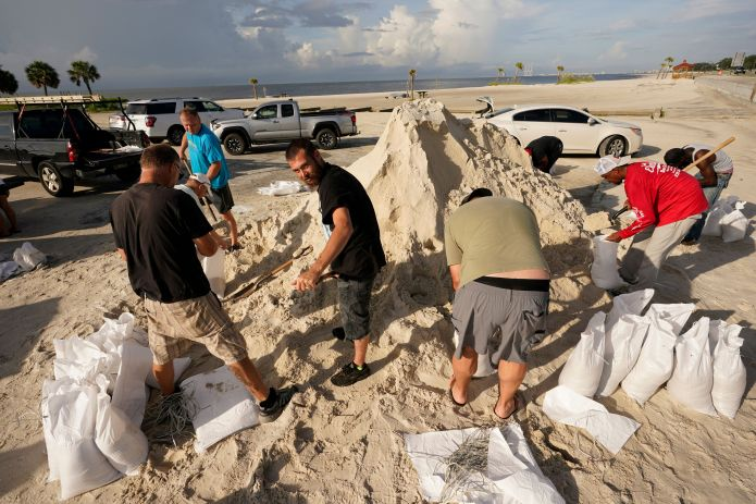 Local residents fill sand bags as they prepare for the expected arrival of Hurricane Ida Saturday, Aug. 28, 2021, in Gulfport