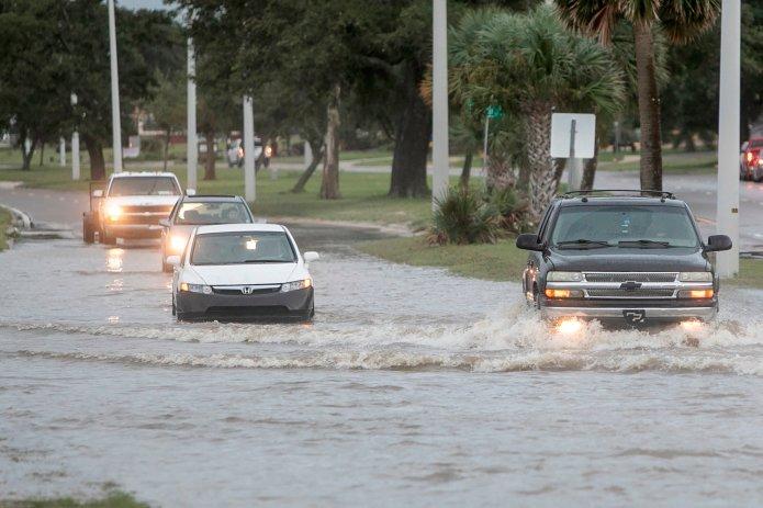 Vehicles drive through Hurricane Ida storm surge floodwater in Biloxi, Miss., on Sunday.