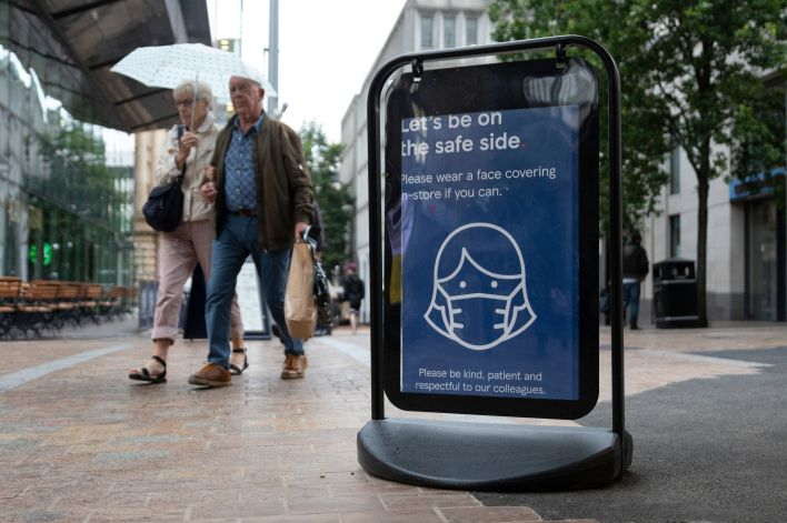 Shoppers pass a sign encouraging people to wear masks to reduce the transmission of the coronavirus outside of a Tesco superm