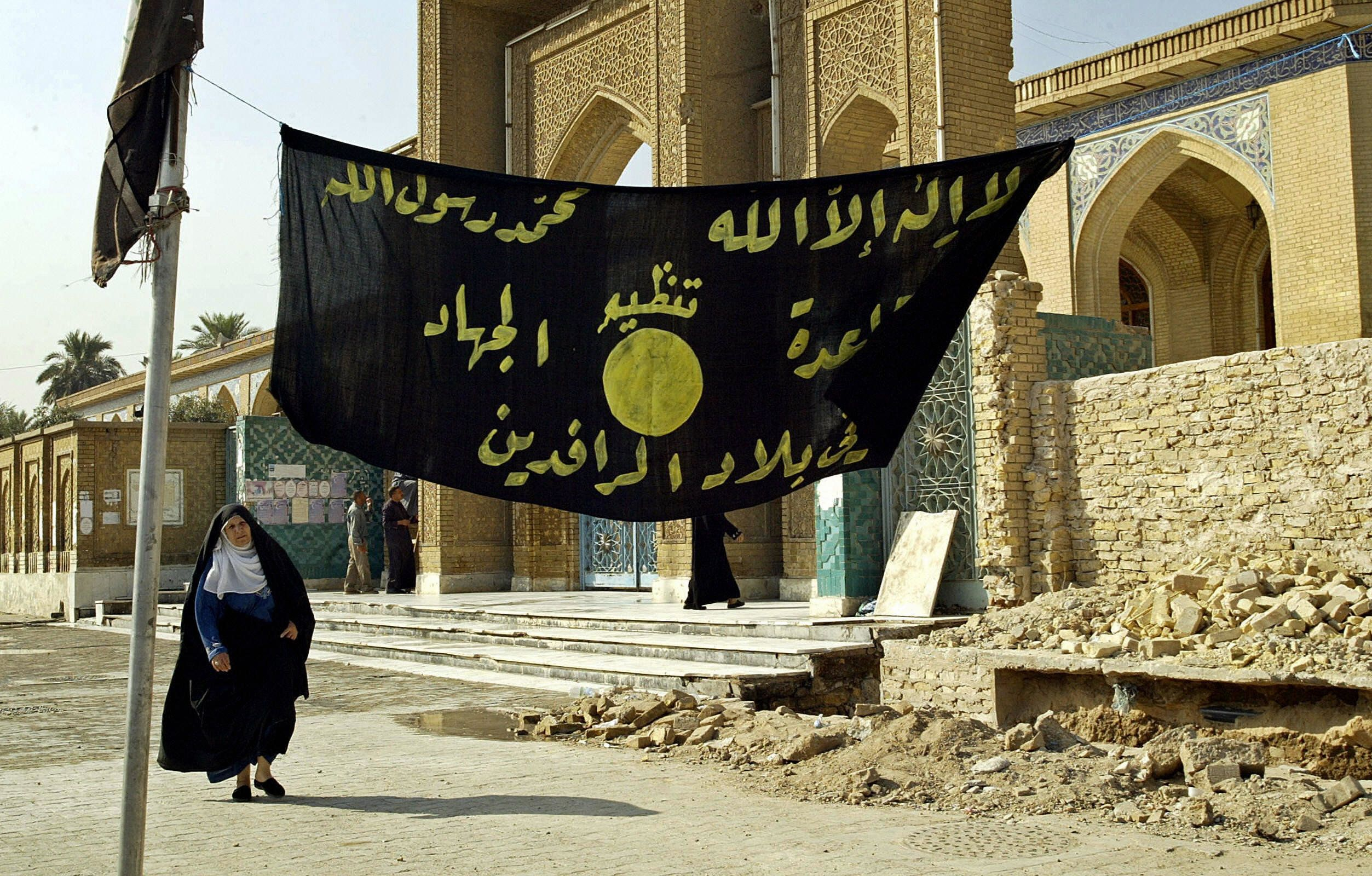 """<span class='image-component__caption' itemprop=""""caption"""">An Iraqi woman walks past a jihadi banner in Baghdad in 2004.</span>"""