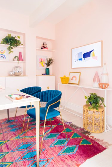 pastel pink home office with bright pink rug and blue velvet office chairs