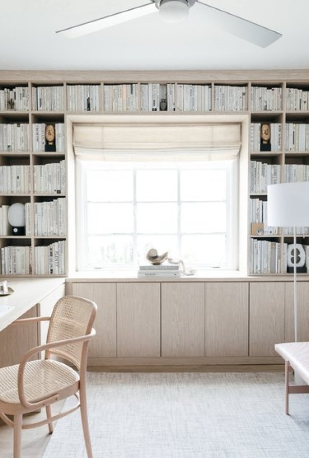 neutral home office with bookshelves and wood cabinets
