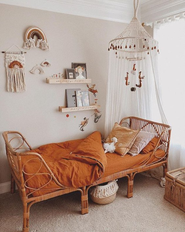 bohemian kids bedroom idea with canopy hanging from ceiling and rust bedding