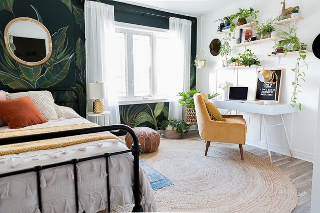 Midcentury modern bohemian bedroom with yellow chair and palm leaf wall mural