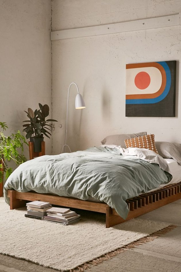 Concrete floors and walls in light color, natural wood platform bed with light gray bedding, white reading lamp, plants, contemporary art print, beige area rug. Basement Bedroom Ideas