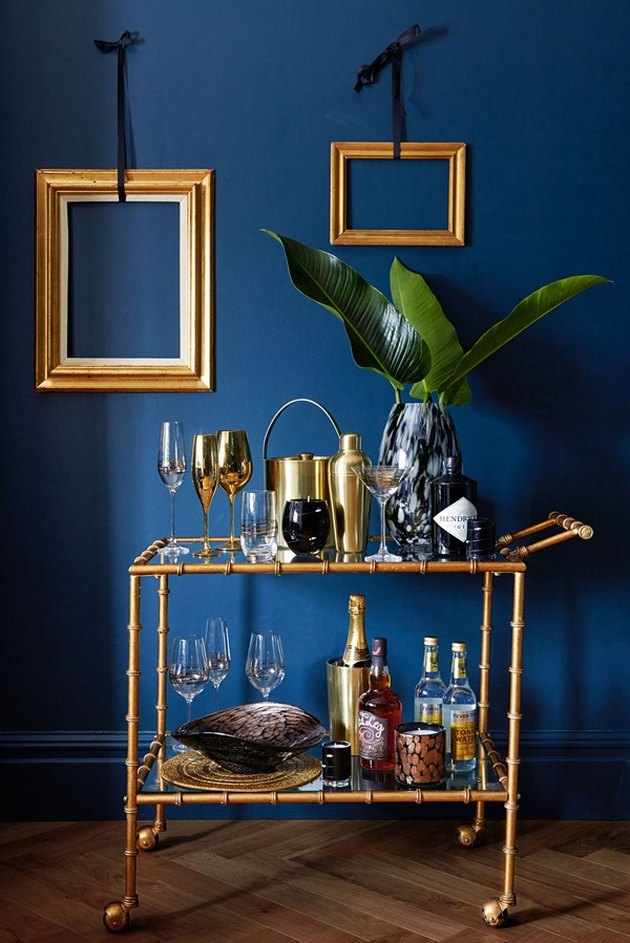 Pantone Color of the Year Classic Blue accent wall with brass picture frames and bar cart