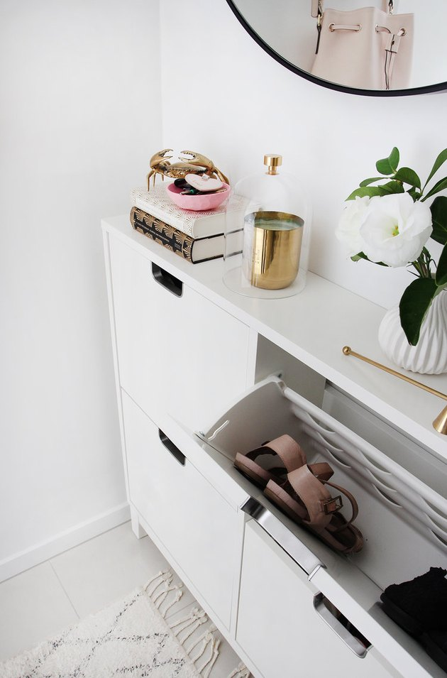 shoe storage cabinet in hallway with round mirror and area rug
