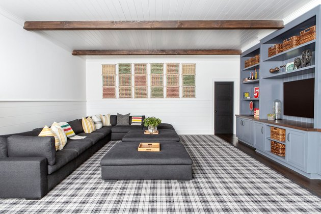 farmhouse family room idea with plaid rug and wood beams