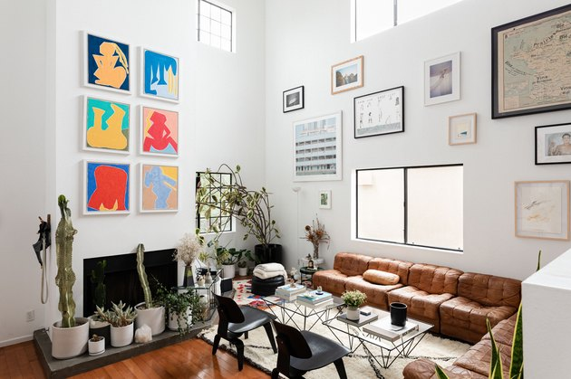 Artwork, tall ceiling, leather couch, and plenty of plants in a modern home