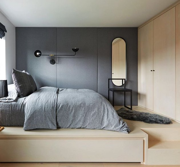 scandinavian bedroom with upholstered walls and light wood cabinetry and flooring
