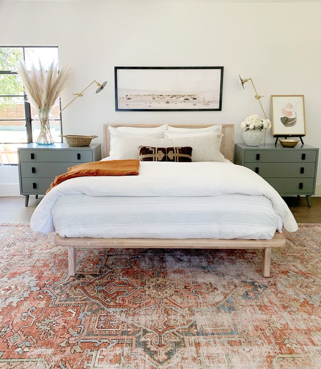 bohemian midcentury bedroom with patterned rug and wall sconces