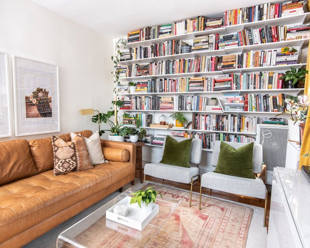 book storage ideas in a living room with wall-to-wall shelving filled with books.