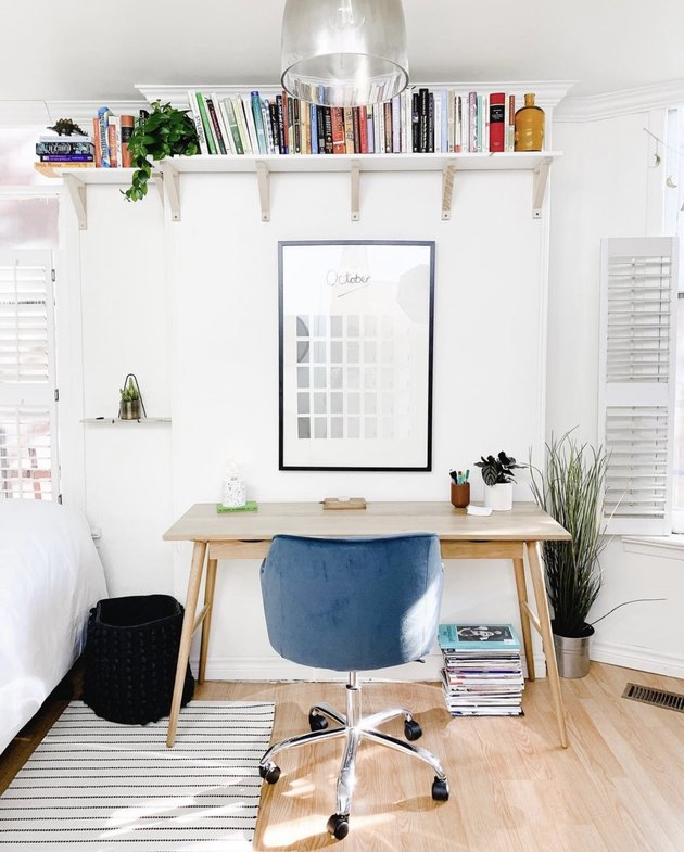 book storage in a room with a desk with a blue chair sits below a wall-mounted bookshelf.