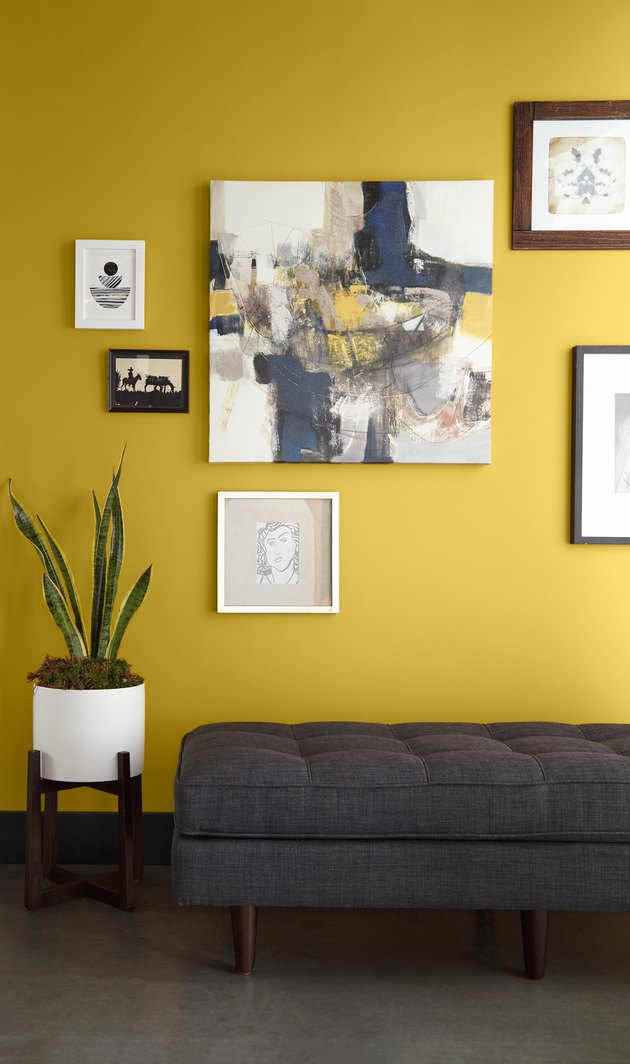 yellow wall with framed art and dark gray couch