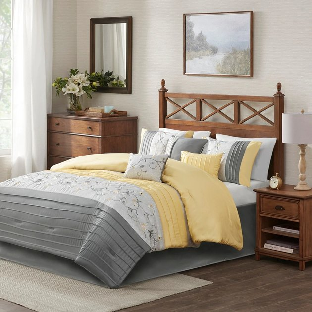 bedroom with gray and yellow bedding and white curtains