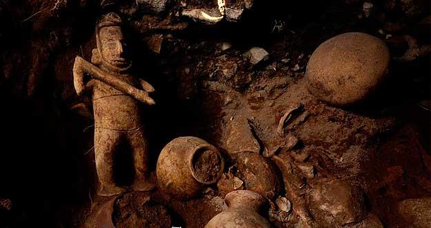 Escultura de un chamán de rostro alargado y arma en mano, junto a vasijas halladas.