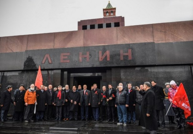 Russian Communists pose for a picture after laying flowers at Lenin's mausoleum on the Red square in Moscow on Nov. 5, 2017, to celebrate the forthcoming 100th anniversary of The Bolshevik Revolution. Russia is set to hold low-key events to mark a century since the 1917 Bolshevik Revolution on Nov. 7, with authorities uncertain how to badess the uprising that led to 70 years of Communist rule.