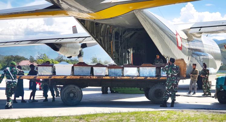 Waktu kehilangan: Petugas Militer Indonesia memuat peti mati ke dalam pesawat pengangkut di Wamena, Papua, pada hari Kamis.  Pasukan keamanan Indonesia telah mengambil mayat 16 orang setelah pembantaian pekerja konstruksi oleh pemberontak separatis di provinsi Papua yang bergolak, militer mengatakan pada hari Kamis.