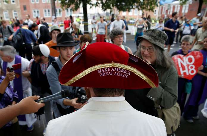 Un suprémaciste blanc répond aux médias, flanqué d'un chapeau colonial où est inscri le slogan de campagne de Donald Trump « Make America Great Again».