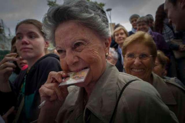 Dans le bureau de vote du quartier de Fort Pienc à Barcelone, les électeurs attendent nombreux sous la pluie battante l'ouverture du bureau.