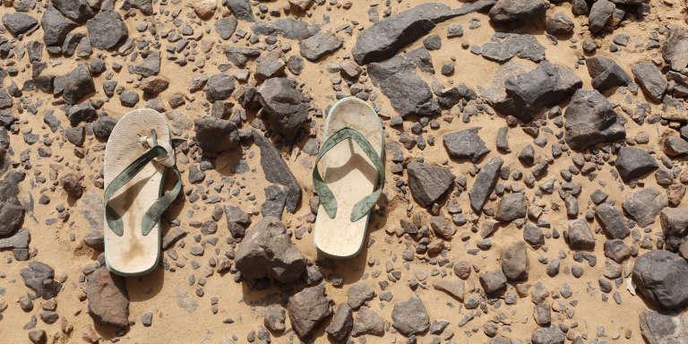 Des tongues appartenant à un migrant subsaharien en plein désert, à la frontière entre l'Algérie et la Libye, en 2014.