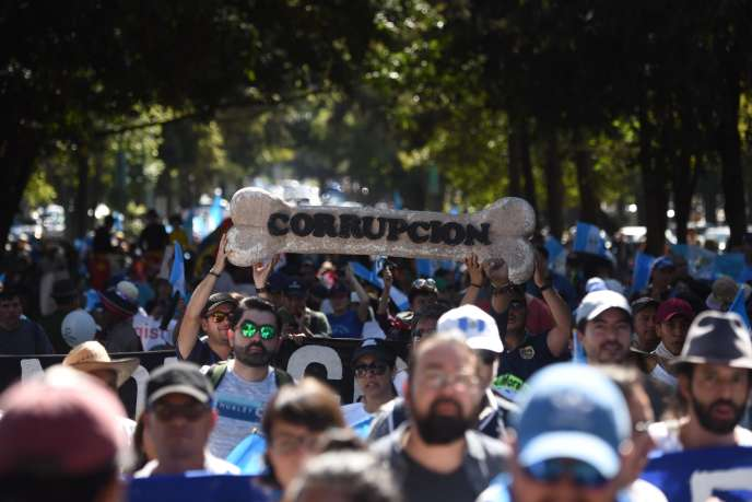 Protesters sway with a giant dog biscuit that & # 39; corruption & # 39; says during a CICIG support demonstration in Guatemala City on 12 January.