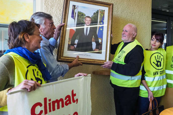Activists ANV COP21 and the mayor of Cabestany (Pyrénées-Orientales), Jean Vila, remove the portrait of Emmanuel Macron hanging in the town hall of the city, February 27, 2019.