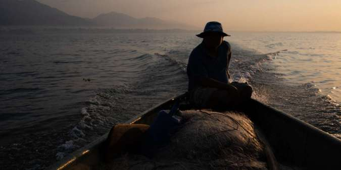 A fisherman who prefers to remain anonymous due to fear of being criminalized, rides his boat at dawn on Lake Izabal. El Estor, Izabal, Guatemala. April 1, 2019.