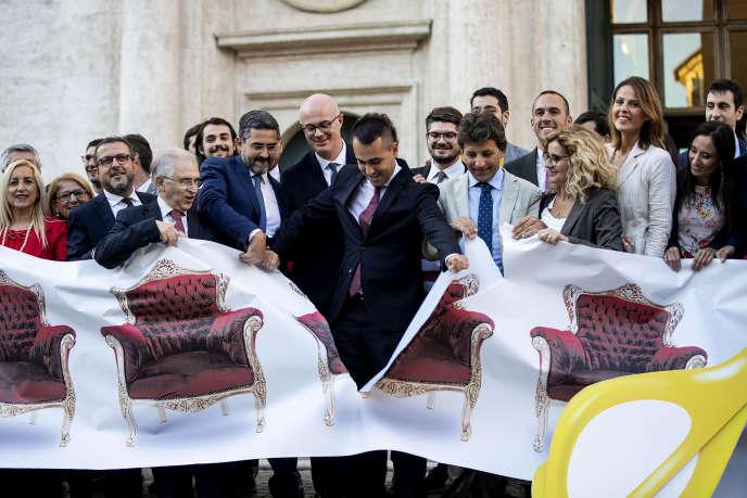 Il ministro degli esteri italiano, Luigi di Maio, che strappa un banner rappresentante dei sedili vuoti, a simboleggiare il numero eccessivo di parlamentari, l ' 8 ottobre, a Roma.