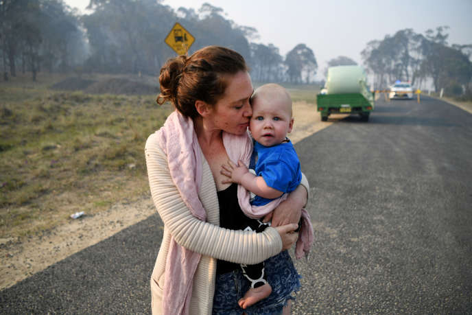 A resident of Wytaliba holds her son in her arms as she waits to return home at a roadblock near Glen Innes, Australia, November 11, 2019.