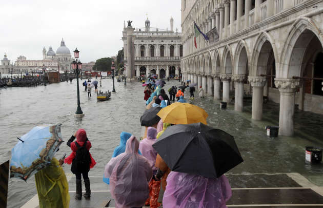 """People walk on a podium set up for the """"high tide"""" in Venice, Italy, on 12 November."""