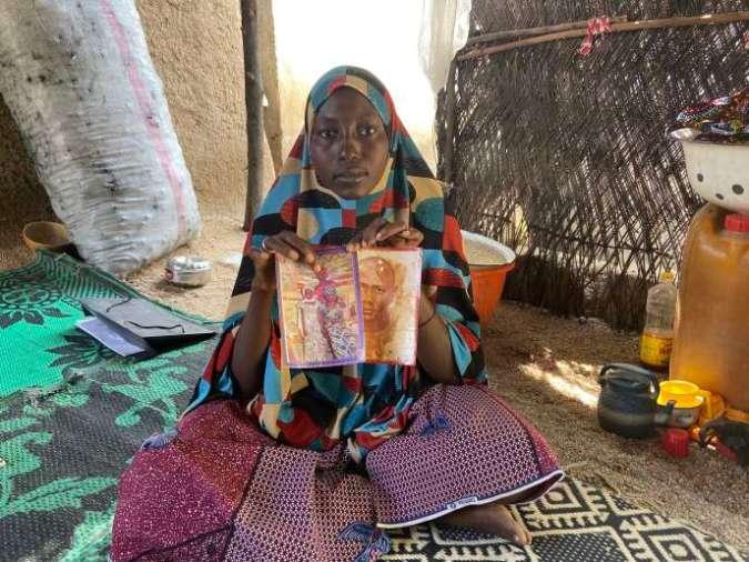 Djallo Ibrahim montre les photos de son mari tué par Boko Haram, et de sa fille, entourée de ses deux tantes, enlevée par le groupe djihadiste. Ici, en novembre 2019.