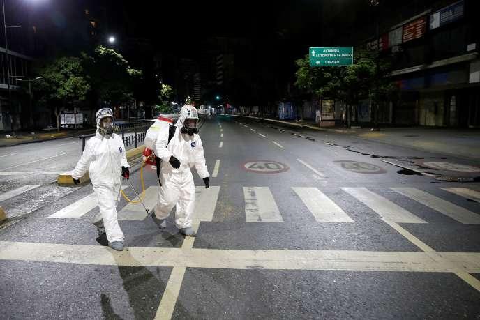 Des travailleurs en tenue de protection marchent dans la rue pendant la quarantaine nationale, à Caracas, le 21 mars.