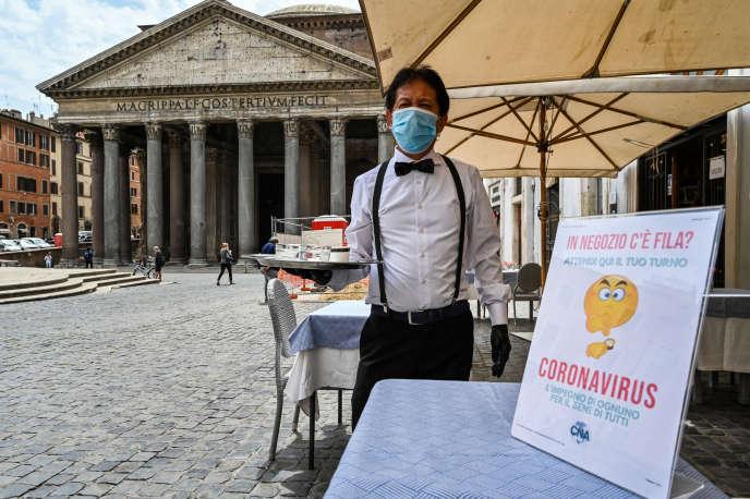 Un server per le strade di Roma, davanti al Pantheon, lunedì 18 maggio. Le caffetterie e i ristoranti della penisola, che erano a rischio di dover attendere fino al 1 ° giugno, sono stati autorizzati a riaprire.