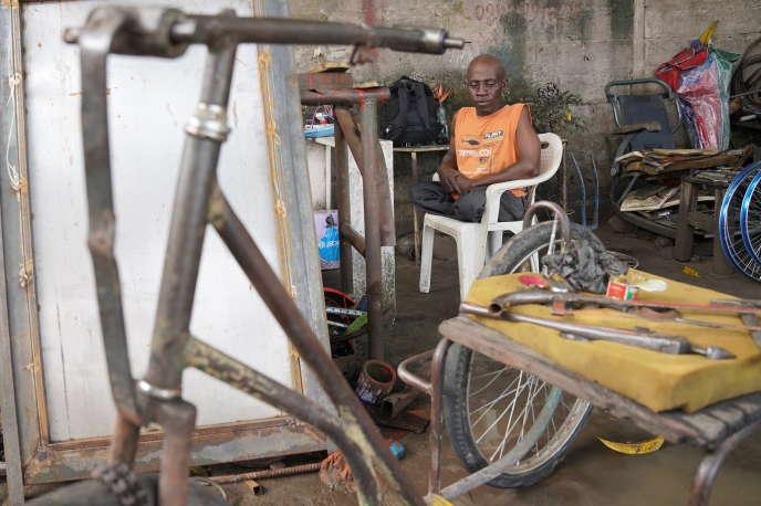 François, handicapé depuis l'âge de 5 ans, attend que les ouvriers réparent son tricycle dans l'atelier de Mafiki Mboyo, à Kinshasa, en novembre 2020.