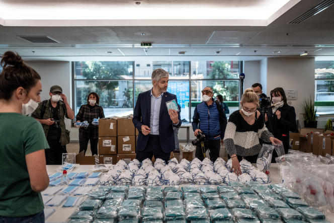 The president (LR) of the Auvergne-Rhône-Alpes region, Laurent Wauquiez (center), presents the action of employees who prepare protection kits and masks for nursing homes in order to prevent the spread of Covid-19, April 3, 2020, in Lyon.