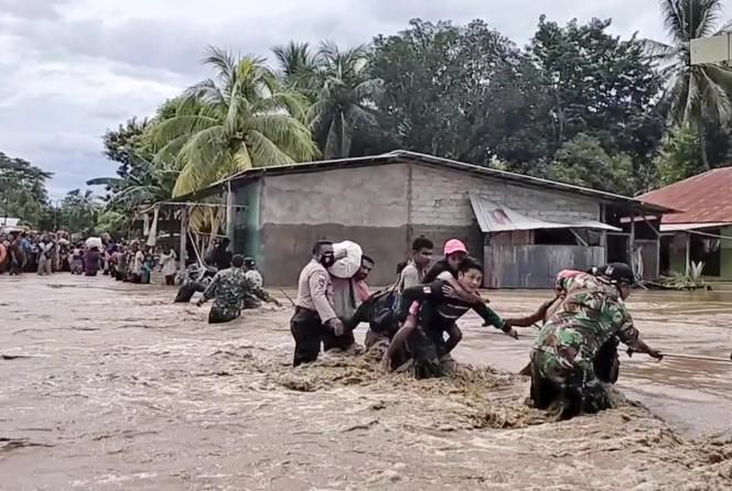 Sur cette image tirée d'une vidéo, des soldats et des policiers aident les habitants à traverser une route inondée à Malaka Tengah, en Indonésie, le 5 avril.