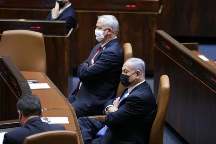 Le premier ministre israélien, Benyamin Nétanyahou, à droite, le ministre de la défense Benny Gantz, au centre, lors de la cérémonie de prestation de serment du 24egouvernement d'Israël, à la Knesset, à Jérusalem, le 6avril 2021.