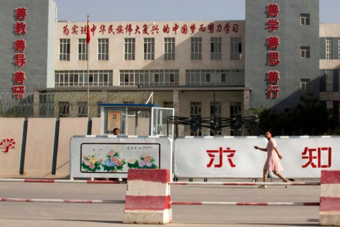 Le 31 août 2018, une femme passe devant un bâtiment présenté comme une école, dans la préfecture deKashgar, au Xinjiang, dans l'ouest de la Chine. Pékin a déclaré avoir condamné à mort deux anciens responsables de la région, y compris l'ancien chef du département de l'éducation, pour séparatisme et corruption.
