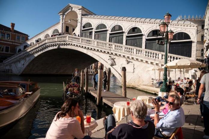 Des touristes sont assis à un café, près du Pont Rialto à Venise, en Italie, le 20 mai 2021.