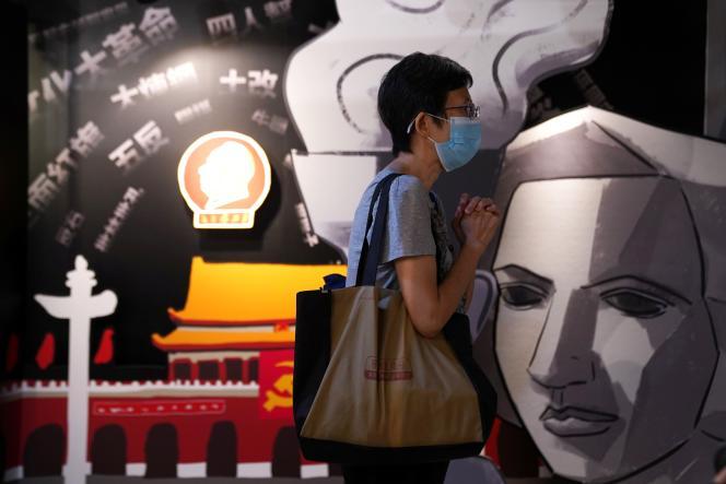 Un visiteur prie à côté d'un tableau représentant la déesse de la démocratie au Musée du 4 juin, qui commémore la répression de la place Tiananmen en 1989, lors de sa réouverture à Hongkong, le 30 mai 2021.