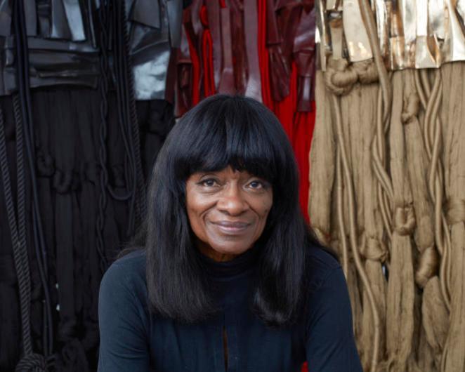 Barbara Chase-Riboud posant devant ses sculptures en hommage à Malcolm X, dans la Michael Rosenfeld Gallery de New York, en 2017.
