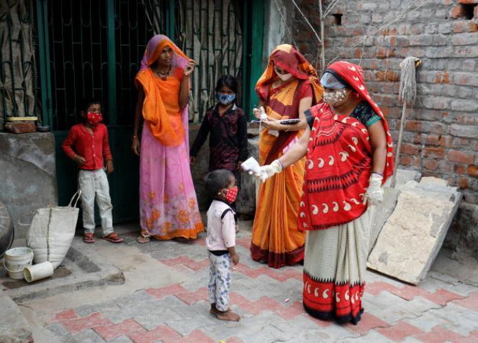 Du personnel de santé prend la température d'un enfant, à Ahmedabad (Inde), le 9 juin 2021.