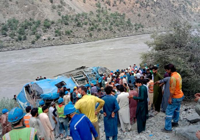 Des habitants et des secouristes rassemblés sur les lieux de l'accident de bus, dans la province pakistanaise de Khyber Pakhtunkhwa, mercredi 14 juillet 2021.