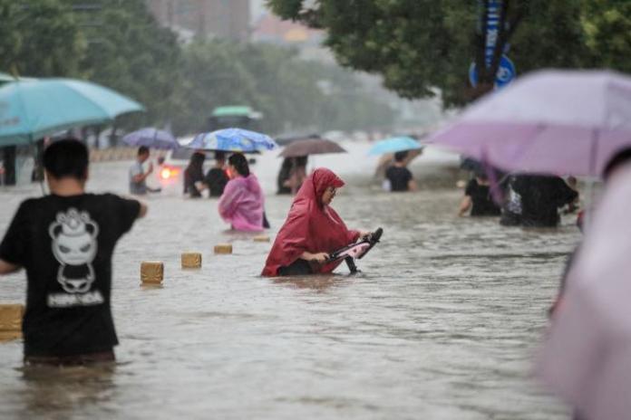 Des habitants de la ville de Zhengzhou, capitale du Henan, en Chine, traversent les rues inondées après de fortes pluies, le 20 juillet 2021.