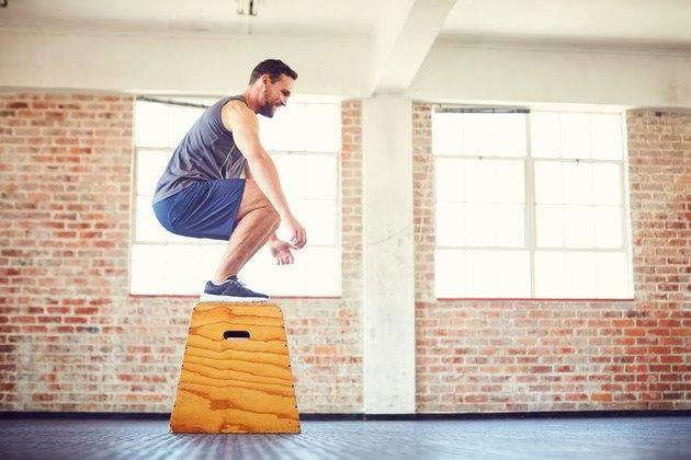 Man box jump squat in the gym