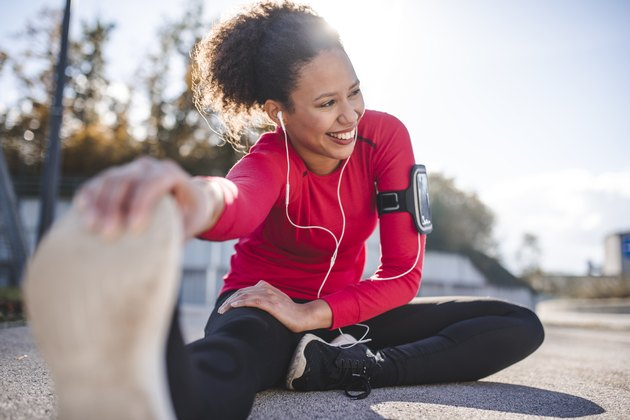 Woman stretching outside wearing arm band and headphones