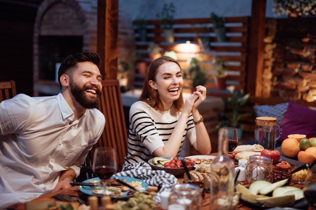 two friends laughing at table of food dining outdoors