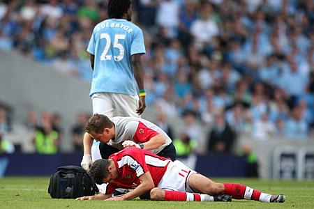 adebayor walks away from his bleeding victim