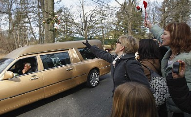 Fans and mourners throw flowers on the hearse that carries the casket of pop singer Whitney Houston at Fairview Cemetery before her burial the day after her funeral